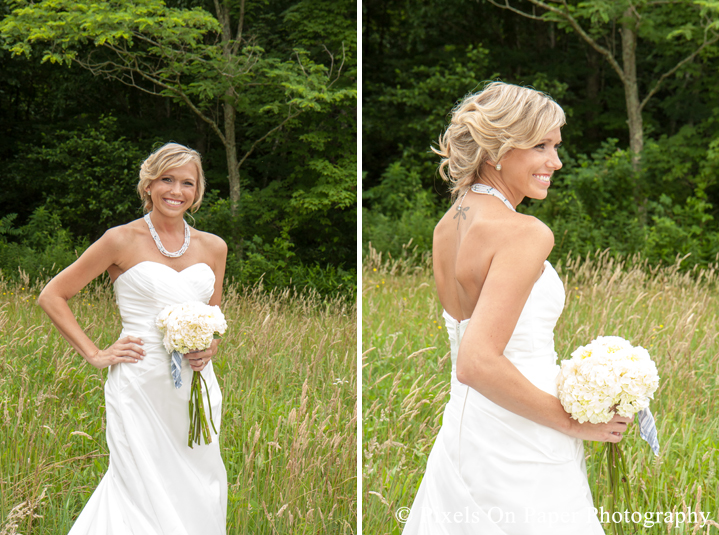 Bride in wedding dress and boots in field at outdoor country mountain wedding at big red barn in west jefferson nc photo