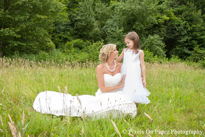Bride in wedding dress with daughter in field at outdoor country mountain wedding at big red barn in west jefferson nc photo