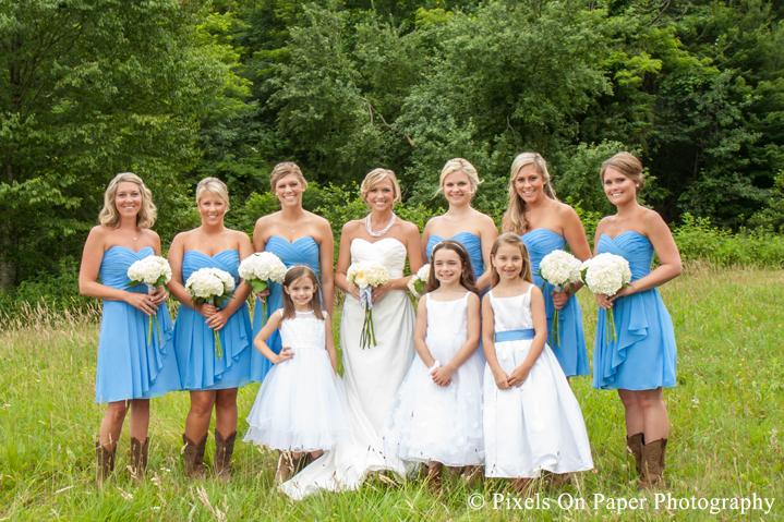 Bride and bridesmaids, wedding dress, blue and boots in field at outdoor country mountain wedding at big red barn in west jefferson nc photo