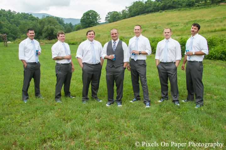 Groom and groomsmen in chuck tailors in field at outdoor country mountain wedding at big red barn in west jefferson nc photo