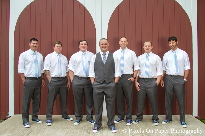 Groom and groomsmen in blue and chuck taylors at outdoor country mountain wedding at big red barn in west jefferson nc photo