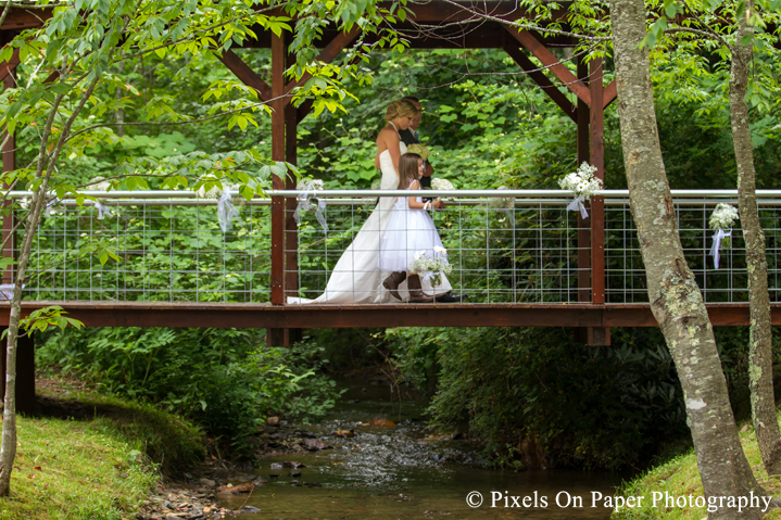 Bride walks covered bridge at outdoor country mountain wedding at big red barn in west jefferson nc photo