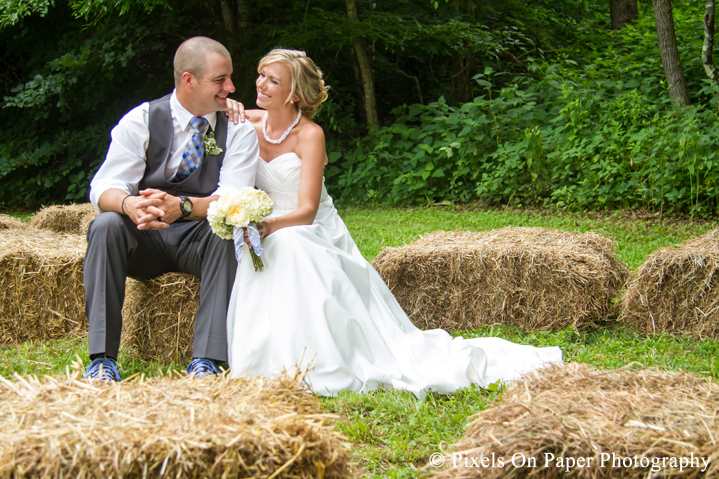 Bride and groom on hay bails for wedding photos at outdoor country mountain wedding at big red barn in west jefferson nc photo