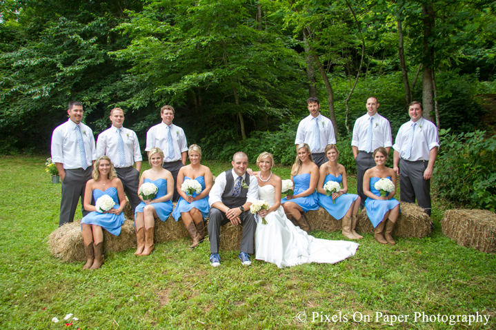 Bride and groom and wedding party on hay bails for wedding photos at outdoor country mountain wedding at big red barn in west jefferson nc photo