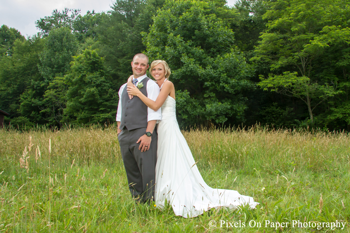 Bride and groom in field for wedding photos at outdoor country mountain wedding at big red barn in west jefferson nc photo