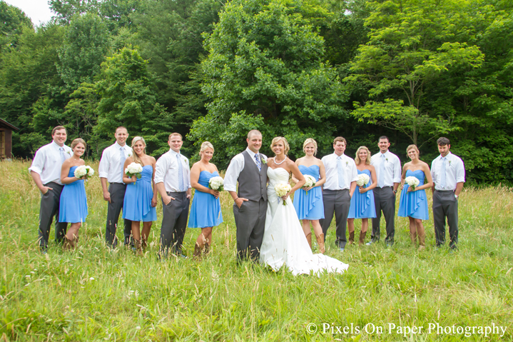 Bride and groom and wedding party in field for wedding photos at outdoor country mountain wedding at big red barn in west jefferson nc photo