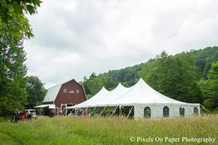 Tent in field at outdoor country mountain wedding at big red barn in west jefferson nc photo
