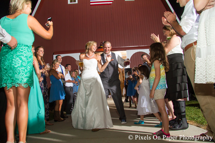 Bride and groom exit at outdoor country mountain wedding at big red barn in west jefferson nc photo