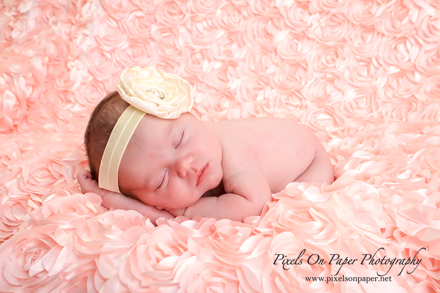 Newborn baby portrait by Pixels On Paper Photographers. Baby Scarlett sleeps in pink during newborn portrait session photo.