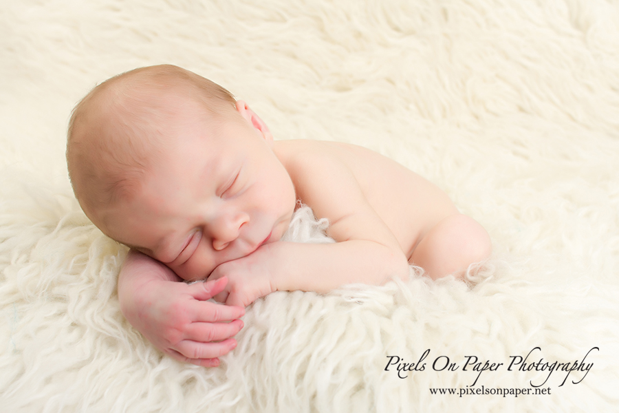 Newborn Baby Portrait Photography by Pixels On Paper Photographers. Baby Liam with eyes closed during his newborn session photo.